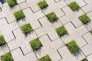 Mooi voorbeeld van parkeerplaats waar Square Cross groenbestrating vrijstaand is gebruikt. Door de betonstenen gedeeltelijk in elkaar te haken, ontstaat een stabiel legpatroon.