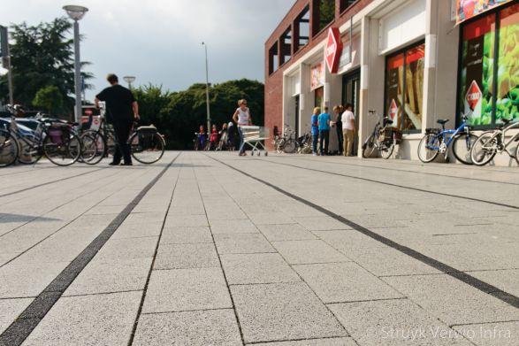 Zwarte en grijze stroken in bestrating|inrichting buitenterrein winkelgebied