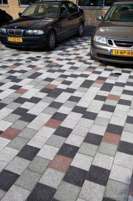 Lappendeken bestrating op parkeerplaats|gekleurde betonstraatstenen