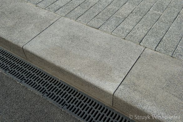Uitgewassen brede trottoirband toegepast bij een bushalte