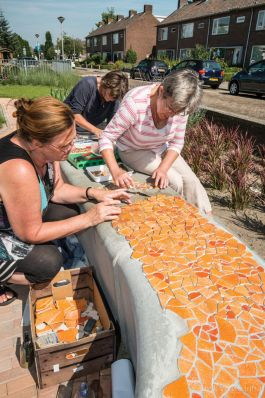 Mozaïek maken op een betonnen bank