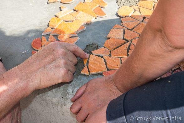 Mozaïek inleggen op een betonnen bank