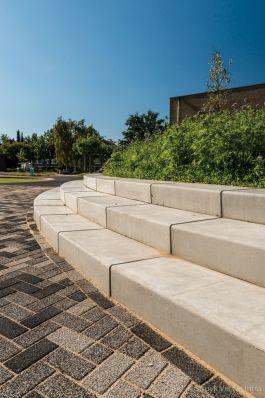 Traptreden van beton rondom groenperk op schoolplein