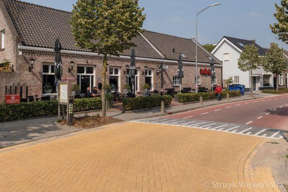 Verhoogd kruispunt met stille straatstenen in dorp