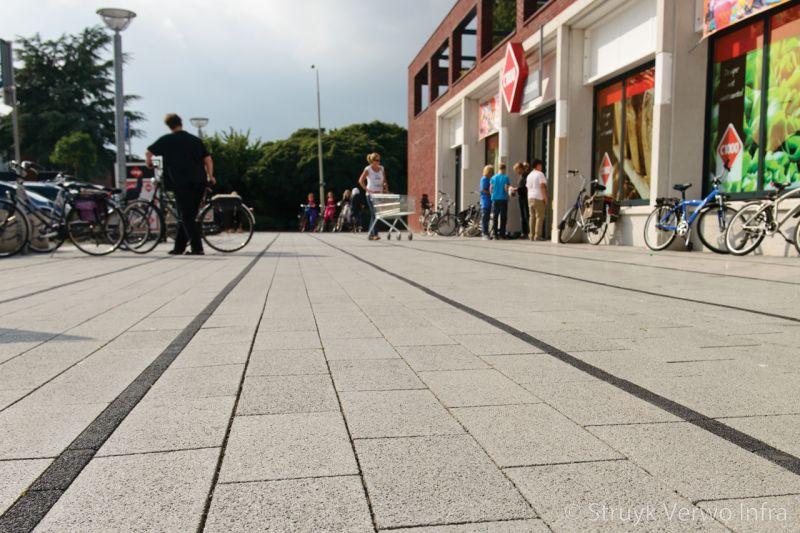 Zwarte en grijze stroken in bestrating inrichting buitenterrein winkelgebied