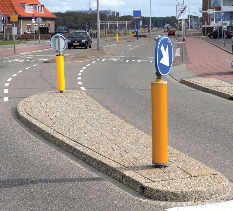 Verkeersgeleider verkeersheuvel met uitgewassen bestrating verkeersbord verplichte rijrichting