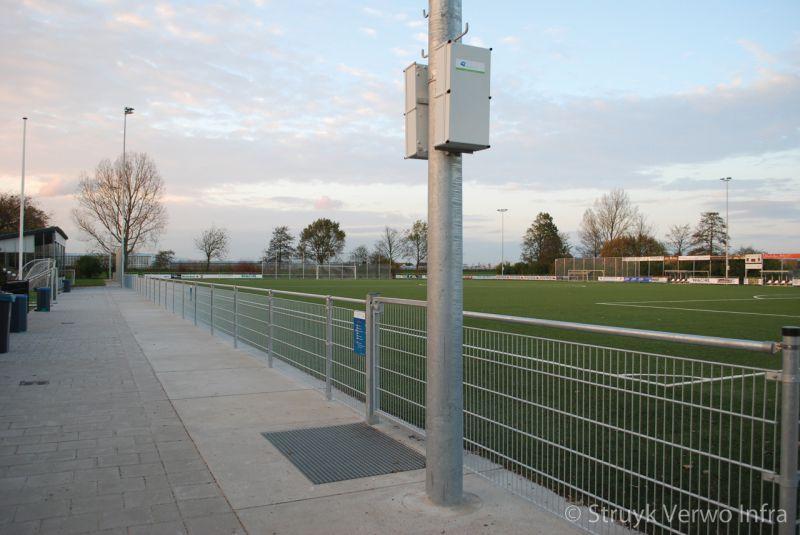 Vloerplaten langs sportveld met schoonlooprooster