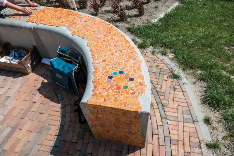 Mozaiek op een betonnen zitelement