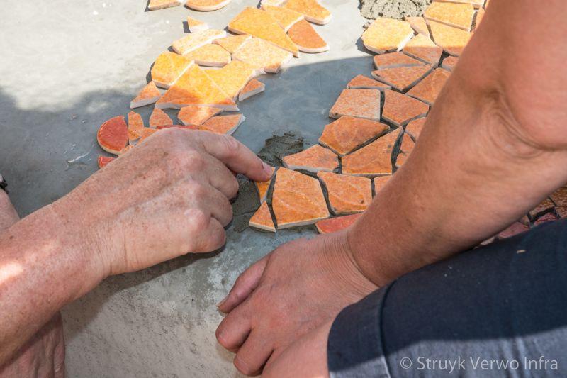 Mozaiek inleggen op een betonnen bank