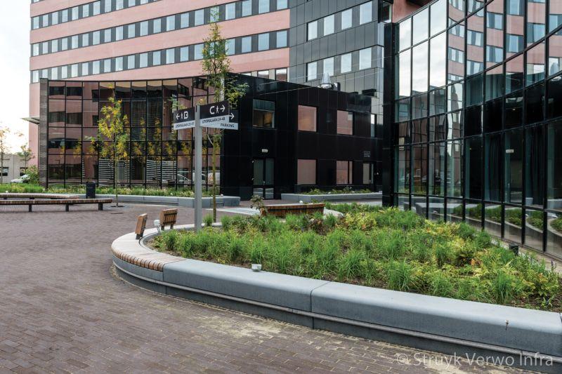 Keerrand van beton langs groen kantorencomplex bolduc den bosch