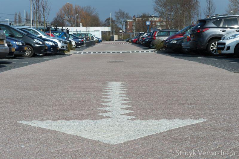 Witte pijl in bestrating bij parkeerterrein