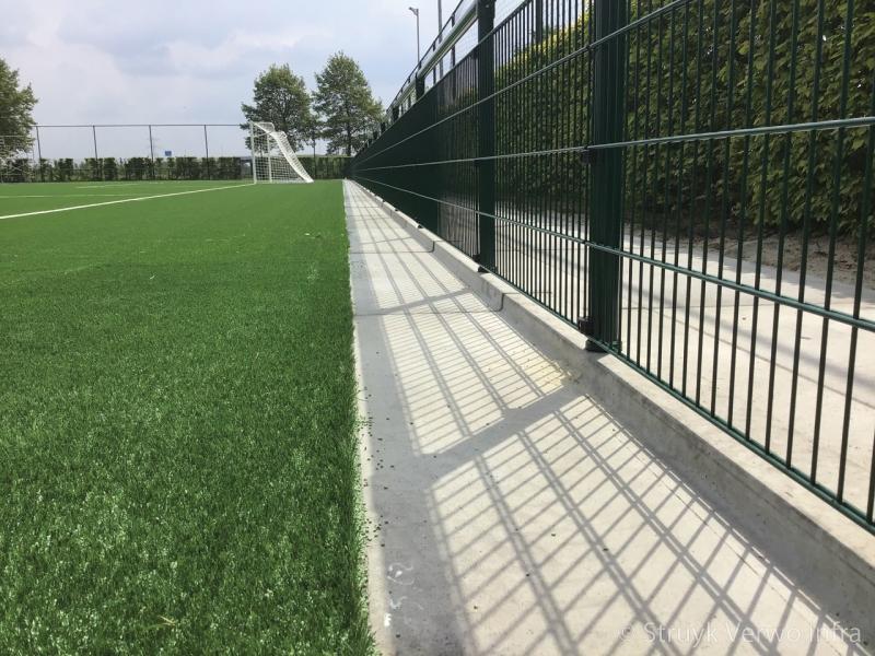 Opsluitplaat met omheining rondom sportvelden verharding rondom kunstgrasvelden