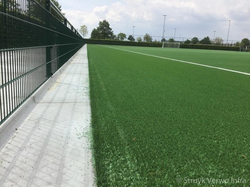 Verharding rondom sportvelden opsluitplaat rubber korrels rondom kunstgrasvelden