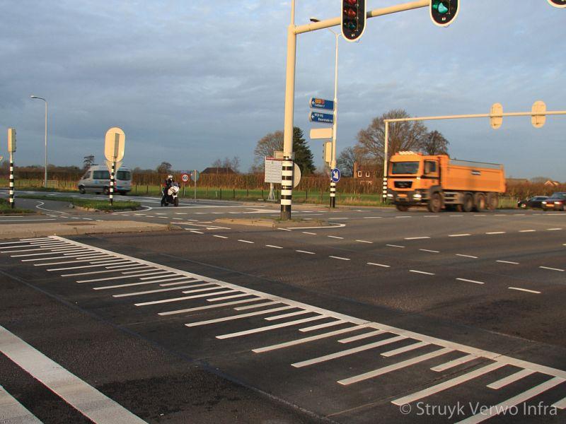 Betonnen verkeersplateaus in asfaltweg voor een stoplicht